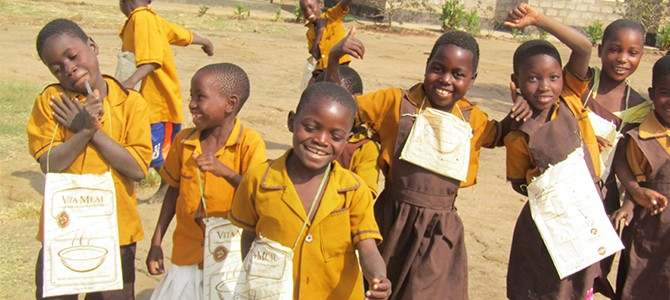 Children in Malawi with repurposed Vitameal bags used to carry school supplies