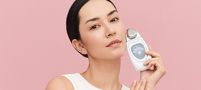 woman holding nu skin facial spa skin care device