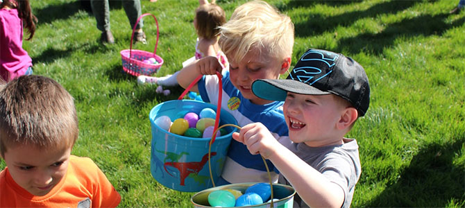 A group of kids show off their buckets full of Easter eggs they collected from the Nu Skin Easter Egg Hunt.