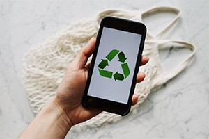 person holding a smartphone with recycle logo on the screen