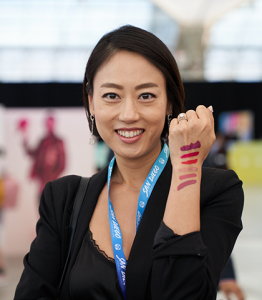 Girl with lipstick swatches on her arm.