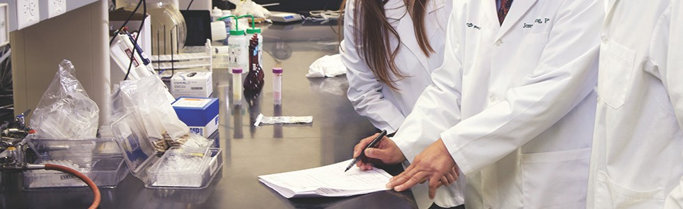 Nu Skin scientists taking notes as they conduct research.
