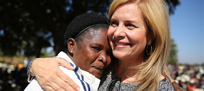 Nu Skin Vice President of Public Affairs Ruth Todd embracing a Malawian mother